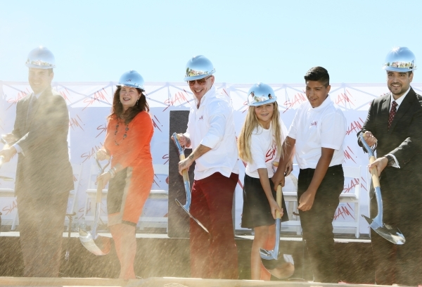 Rapper Pitbull, third from left, participates in a groundbreaking ceremony for Sports Leadership and Management (SLAM!) charter middle and high school Friday, Oct. 2, 2015, near the Russell Road R ...
