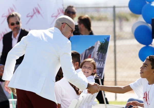 Rapper Pitbull shakes hands with a student at the start of a groundbreaking ceremony for Sports Leadership and Management (SLAM!) charter middle and high school Friday, Oct. 2, 2015, in Henderson. ...