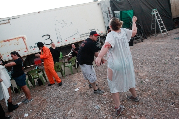 "Peter Basham, center, applies fake blood to Crystalena Nightengale during a dress rehearsal at the ""Gates of Hell"" haunted house, which is one of the Trilogy of Terror haunted houses run ..."