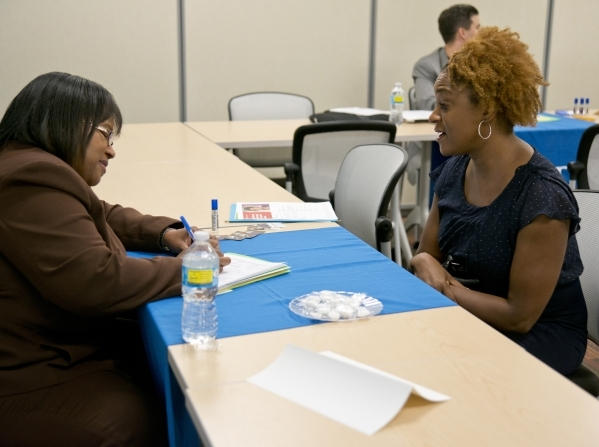 Carol Neal, right, answers questions during an interview with Northey Henderson during a Clark County School District substitute teacher hiring event at The University of Phoenix building in Summe ...