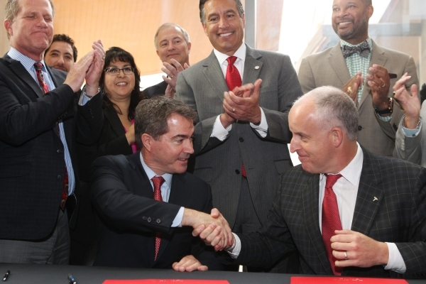 UNLV president Len Jessup, left, and Diarmuid O'Connell, vice president at Tesla, shake hands after a ceremonial signing of a $1 million, 5-year-agreement between UNLV and Tesla to fund rese ...