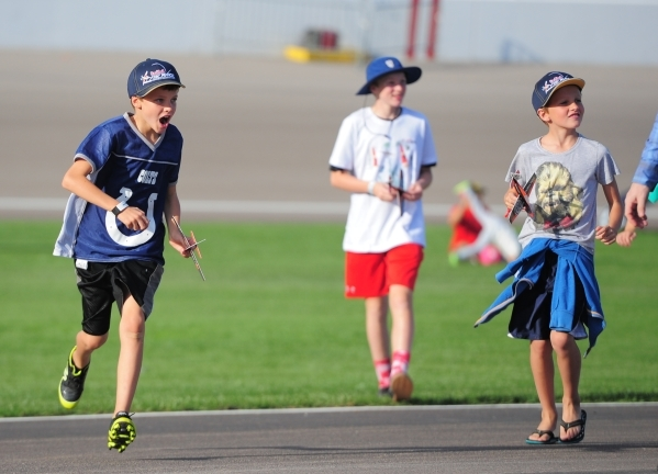 Kids run to catch a glimpse of a plane being pushed to the starting line during the Red Bull Air Race World Championship Series race at the Las Vegas Motor Speedway on Saturday, Oct. 17, 2015. Bre ...