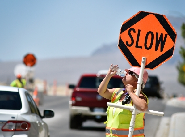 Flagger Shayne Boley takes a drink of water as she guides vehicles though a construction zone on North Grand Canyon Drive in Las Vegas on Tuesday, June 16, 2015. Boley drinks a dozen bottles of wa ...