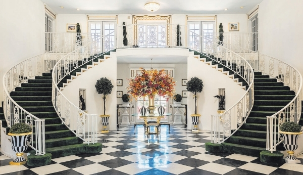 "The ""Gone With the Wind""-inspired staircase in Hartland Mansion in Las Vegas leads to the second floor and two suites that offer mini-balconies looking out at the grand entry's bla ..."