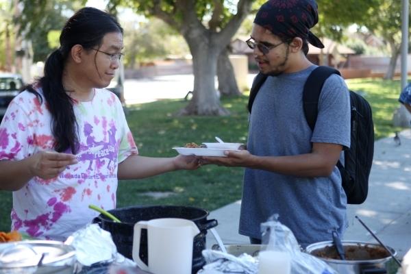 Ming Lai, left, volunteer with Food Not Bombs, serves a meal for Jonas Rand at Huntridge Circle Park in Las Vegas on Sunday, Oct. 11, 2015. (Erik Verduzco/Las Vegas Review-Journal)