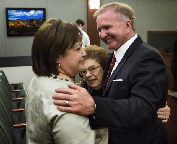 Attorney Robert Eglet, right, hugs Mary Iorio, center, the widow of Maurice Iorio, who died from bladder cancer complications in November 2013, and Pamela Kann, Maurice Iorio's sister, after ...