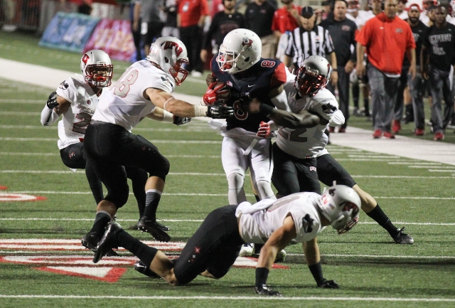 Fresno State wide receiver Da'Mari Scott (8) is taken down by UNLV defense including UNLV linebacker Bailey Laolagi (48) and UNLV running back David Greene (22) during a football game at Bul ...