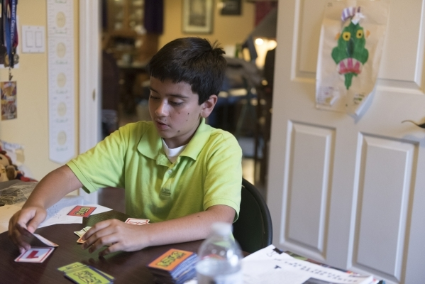Eleven-year-old J.C. Hill works through an exercise during his therapy sessionwith Roo Abdel-Al, a supervising consultant at The Lovass Center, at Hill's residence in Las Vegas Wednesday, Oc ...