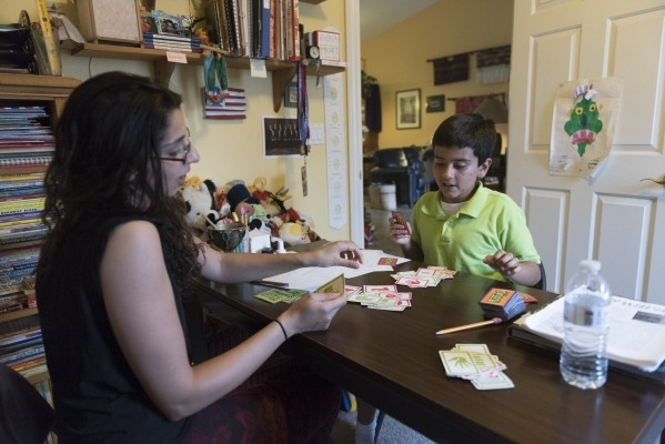 Roo Abdel-Al, left, supervising consultant with The Lovass Center, conducts a therapy session for 11-year-old J.C. Hill at Hill's residence in Las Vegas Wednesday, Oct. 14, 2015. Jason Oguln ...