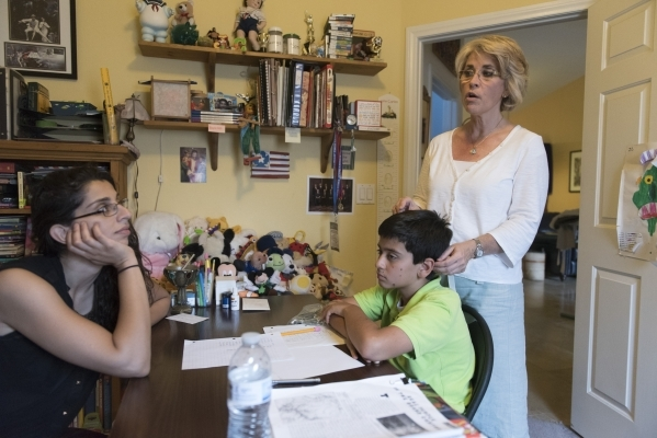 Stephanie Hill, right, and J.C. Hill speak with Roo Abdel-Al, supervising consultant with The Lovass Center, during 11-year-old J.C. Hill's therapy session at Stephanie Hill's residenc ...