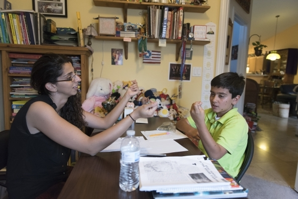 Roo Abdel-Al, left, supervising consultant with The Lovass Center holds a therapy session for 11-year-old J.C. Hill at Hill's residence in Las Vegas Wednesday, Oct. 14, 2015. Jason Ogulnik/L ...