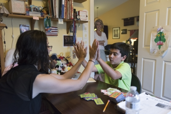 Roo Abdel-Al, left, supervising consultant with The Lovass Center conducts a therapy session for 11-year-old J.C. Hill, right, while Stephanie Hill watches at Hill's residence in Las Vegas W ...