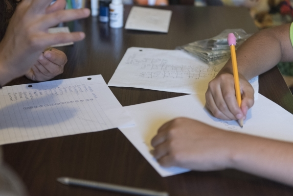 Eleven-year-old J.C. Hill writes during his therapy session with Roo Abdel-Al, a supervising consultant at The Lovass Center, at Hill's residence in Las Vegas Wednesday, Oct. 14, 2015. Jason ...