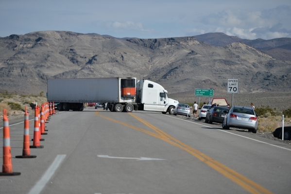 A tractor-trailer turns away from a roadblock as Nye County Sheriff and NHP officers divert traffic from U.S. Highway 95 to Nevada State Route 160 on Monday, Oct. 19, 2015, north of Las Vegas. Bre ...