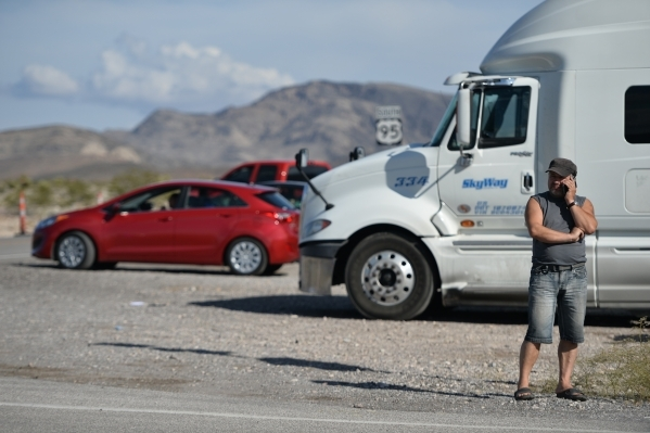 A motorist talks on his phone as Nye County Sheriff and NHP officers divert traffic from U.S. Highway 95 to Nevada State Route 160 on Monday, Oct. 19, 2015, north of Las Vegas. Brett LeBlanc/Las V ...