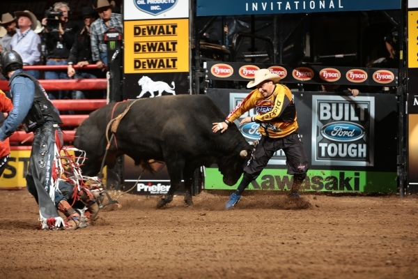 Tanner Byrne attempts to ride Martinez Bucking Bulls's Born Sinner and Frank Newsom steps in during the championship round of the OKC Built Ford Tough series PBR. Photo by Andy Watson