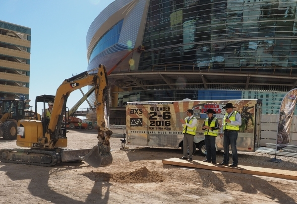 Rick Arpin, Senior Vice President of Entertainment and Development for MGM Resorts, from left, bull rider Reese Cates PBR CEO Sean Gleason watch as a load of dirt from the Thomas and Mack Center i ...