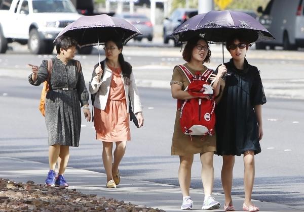 Tourists hold umbrellas to protect themselves from sun as they walk along Sahara Avenue on Tuesday, Oct. 27, 2015, in Las Vegas. (Bizuayehu Tesfaye/Las Vegas Review-Journal Follow @bizutesfaye)