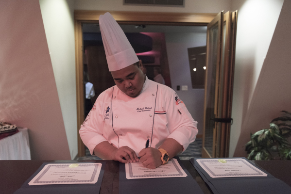 Chef Michael Gabriel signs certificates of completion during the 40th graduation ceremony for The Salvation Army's Lied Vocational Program at Russell's Restaurant at College of Souther ...
