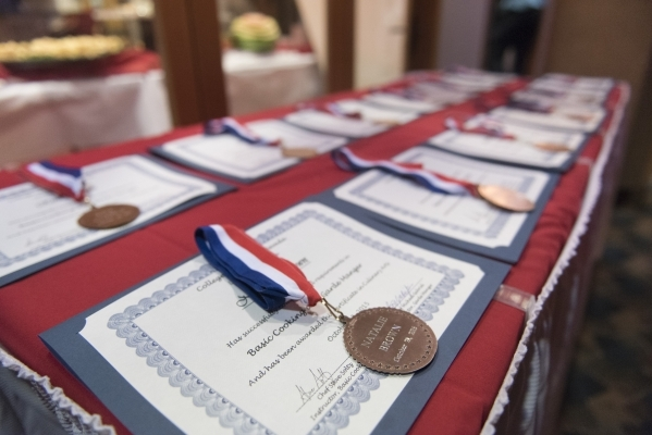Certificates of completion and medals are shown during the 40th graduation ceremony for The Salvation Army's Lied Vocational Program at Russell's Restaurant at College of Southern Neva ...
