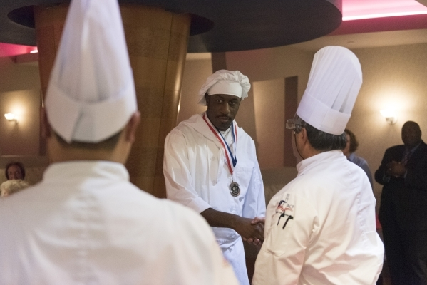 Alfonso Highsmith, center, receives his medal and certificate of completion during the 40th graduation ceremony for The Salvation Army's Lied Vocational Program at Russell's Restaurant ...