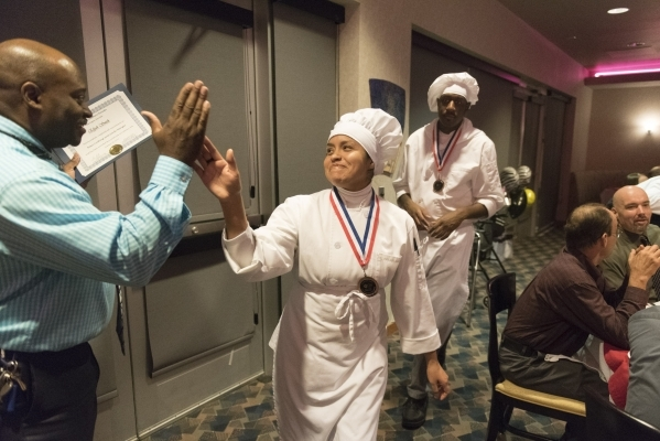 Monica Sheffield, center, high fives Ernest Smith, left, case manager for The Salvation Army during the 40th graduation ceremony for The Salvation Army's Lied Vocational Program at Russell&l ...