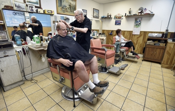 Barber Jerry Stump combs out his customer, Tim Vanca's hair, after a trim at the West Hill Barber Shop on Tuesday, Oct. 27, 2015, in Las Vegas. Stump, a Las Vegas resident since 1942, has be ...