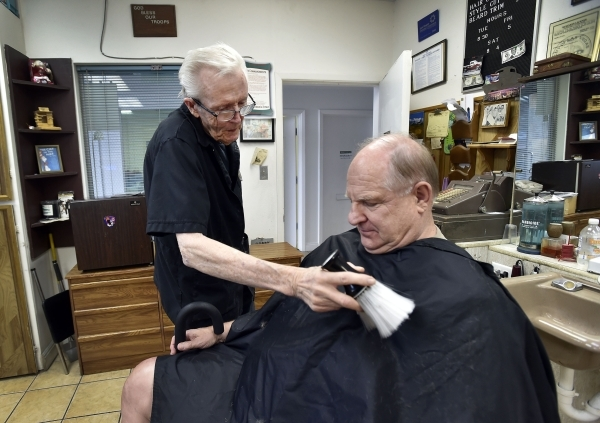 Barber Jerry Stump brushes off his customer Tim Vanca after a trim at the West Hill Barber Shop on Tuesday, Oct. 27, 2015, in Las Vegas. Stump, a Las Vegas resident since 1942, has been cutting ha ...