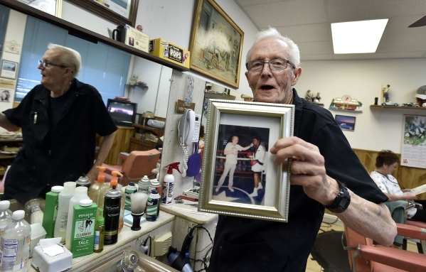 Barber Jerry Stump displays a photograph of himself punching a wax figure of Muhammad Ali at his West Hill Barber Shop on Tuesday, Oct. 27, 2015, in Las Vegas. Stump, a Las Vegas resident since 19 ...
