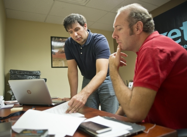 Matt Krueger, left, walks potential employee Simon Swinton through paperwork during an employee intake event for Get Me, a new ridehail company, near Sandhill Road and Patrick Lane in Las Vegas on ...