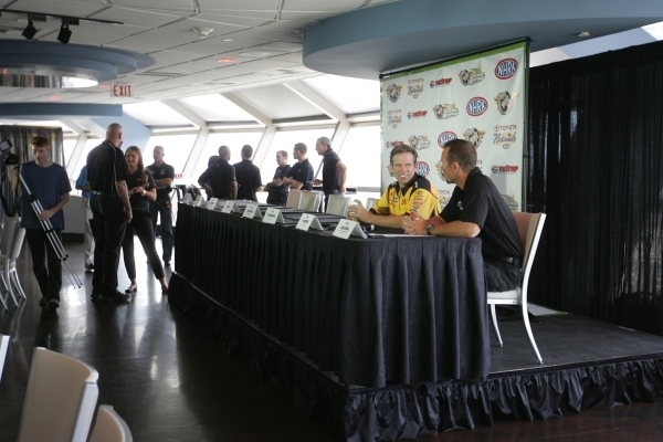 NHRA Funny Car drivers Del Worsham, center right and Jack Beckman, far right, speak with each other before a press conference for the NHRA Toyota Nationals held at the Stratosphere on Thursday, Oc ...
