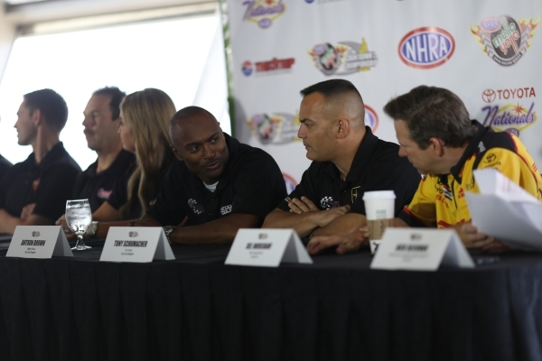 Top Fuel driver Antron Brown, center, talks to funny car driver Del Worsham, right, during a press conference for the NHRA Toyota Nationals held at the Stratosphere on Thursday, Oct. 29, 2015 in L ...