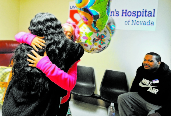 Tiffany Ward, center, receives a hug by Shimiaka Chadwick as her husband, Brandon Ward, looks on in the waiting area at the University Medical Center Children's Hospital of Nevada on Tuesday ...