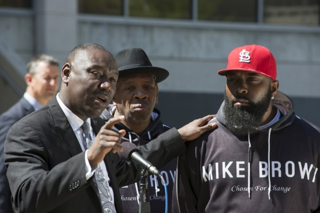 Michael Brown's family attorney Benjamin Crump puts his hand on the shoulder of Michael Brown Sr. during the announcement the Brown family has filed a wrongful death lawsuit against the city ...