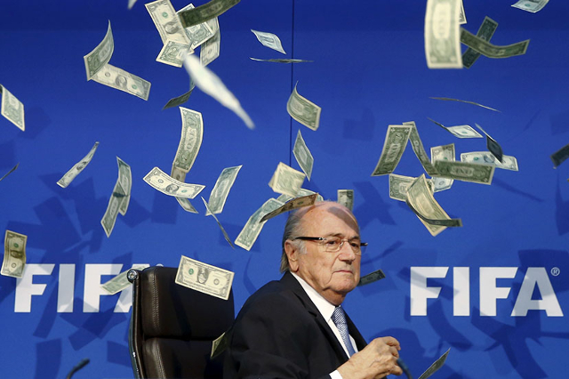 British comedian known as Lee Nelson (unseen) throws banknotes at FIFA President Sepp Blatter as he arrives for a news conference after the Extraordinary FIFA Executive Committee Meeting at the FI ...