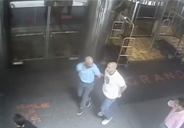 Ex-tennis star James Blake is shown handcuffed and led away from the view of the camera by a NYPD officer James Frascatore (R) in front of the Grand Hyatt hotel in New York on September 9, 2015 in ...