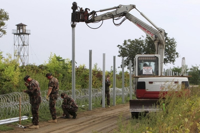 Hungarian army soldiers erect a fence on the border with Croatia near Sarok, Hungary, September 20, 2015.  (Reuters/Bernadett Szabo)