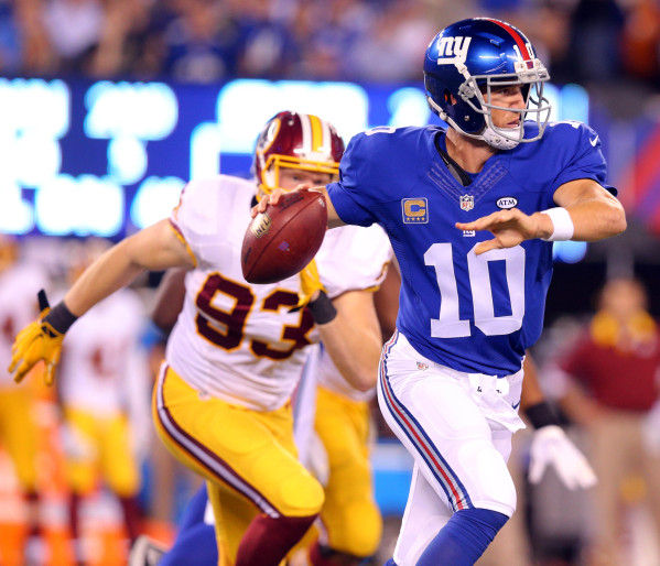 Sep 24, 2015; East Rutherford, NJ, USA; New York Giants quarterback Eli Manning (10) scrambles away from Washington Redskins linebacker Trent Murphy (93) during the second quarter at MetLife Stadi ...