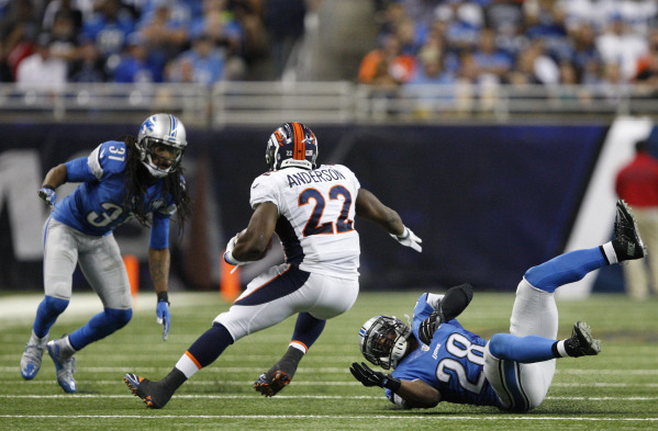 Sep 27, 2015; Detroit, MI, USA; Denver Broncos running back C.J. Anderson (22) carries the ball as Detroit Lions cornerback Quandre Diggs (28) and cornerback Rashean Mathis (31) defend during the  ...