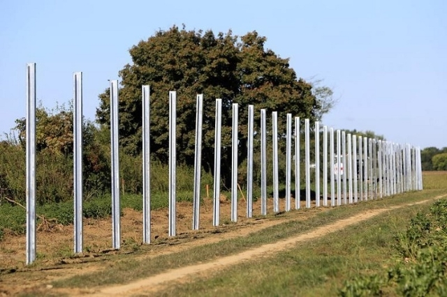 The poles of a new fence on the border with Croatia are set up near Beremend, Hungary, September 21, 2015. (Reuters/Bernadett Szabo)