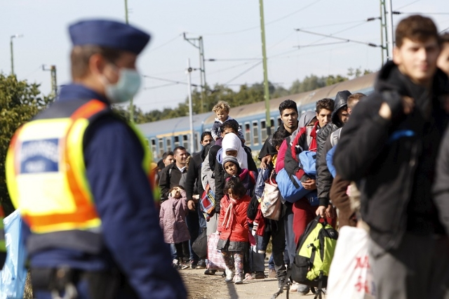 Migrants queue to board a train at the railway station in Zakany, Hungary October 1, 2015. (Reuters/Bernadett Szabo)