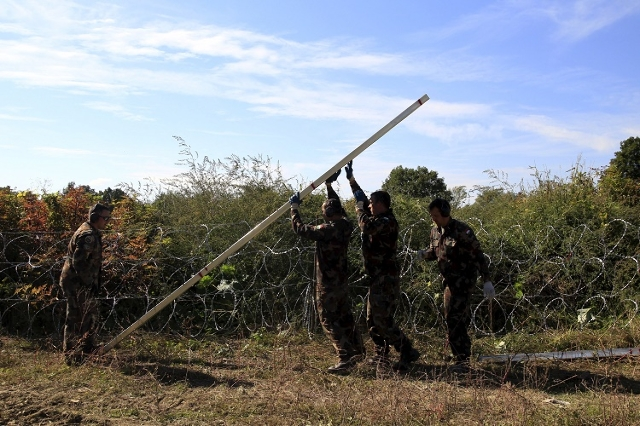 Hungarian army soldiers fix the poles of a new fence on the border with Croatia near Zakany, Hungary, October 1, 2015. (Reuters/Bernadett Szabo)