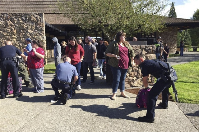 Police officers inspect bags as students and staff are evacuated from campus following a shooting incident at Umpqua Community College in Roseburg, Oregon October 1, 2015. (Reuters/Michael Sulliva ...