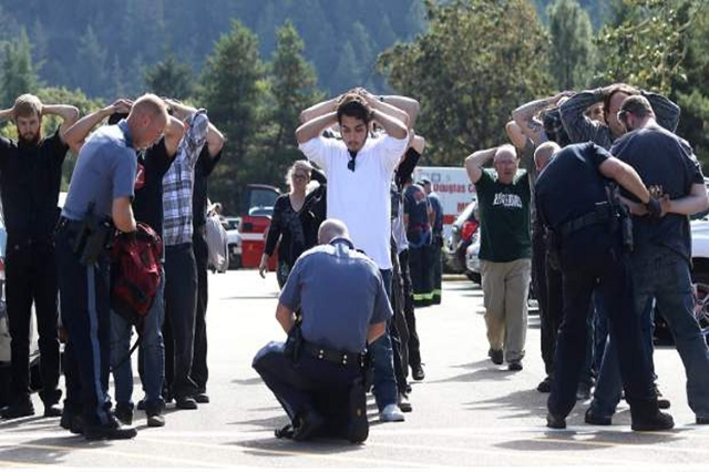Police officers inspect bags as students and staff are evacuated from campus following a shooting incident at Umpqua Community College in Roseburg, Oregon October 1, 2015. (Reuters/Michael Sullivan)