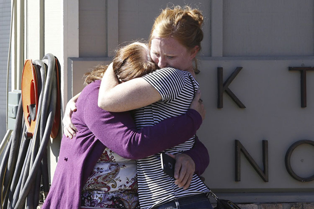 Umpqua Community College alumnus Donice Smith (L) is embraced after she said one of her former teachers was shot dead, near the site of a mass shooting at Umpqua Community College in Roseburg,Oreg ...
