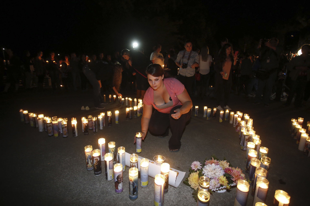 A woman places a candle as people take part in candle light vigil following a mass shooting at Umpqua Community College in Roseburg, Oregon October 1, 2015. A gunman opened fire at a community col ...
