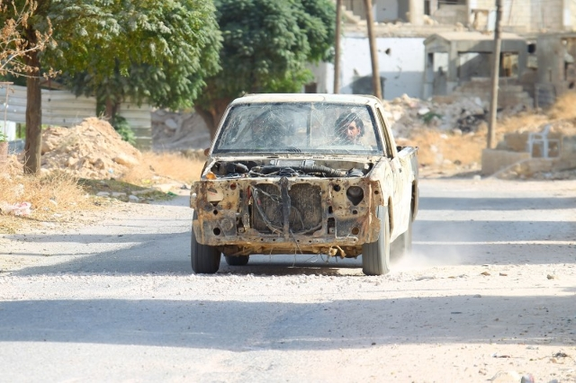 Rebel fighters drive a damaged vehicle in Latamneh city that was hit on Wednesday by Russian air strikes, in the northern countryside of Hama, Syria October 2, 2015.  REUTERS/Ammar Abdullah