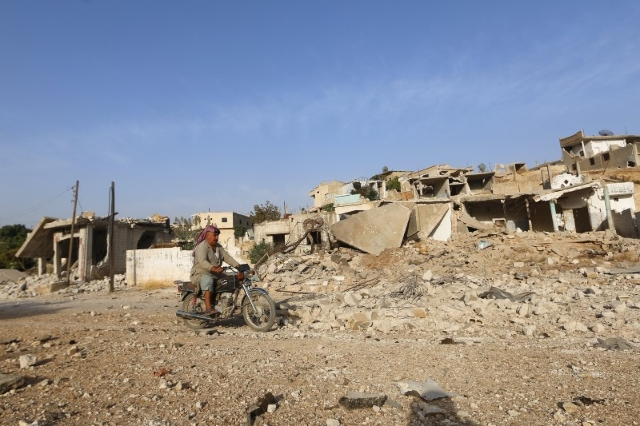 A man rides on a motorbike past damaged buildings in Latamneh city that was hit on Wednesday by Russian air strikes, in the northern countryside of Hama, Syria October 2, 2015.   REUTERS/Ammar Abd ...