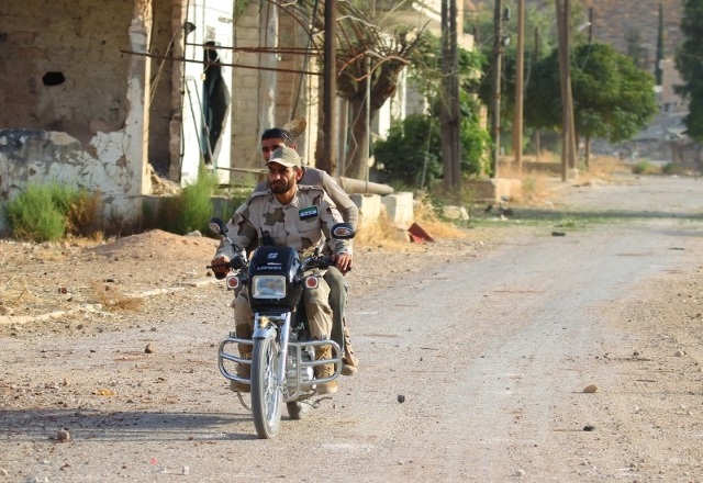 Fighters from Tajammu al-Izza group, part of the Free Syrian Army, ride on a motorbike in Latamneh city that was hit on Wednesday by Russian air strikes, in the northern countryside of Hama, Syria ...
