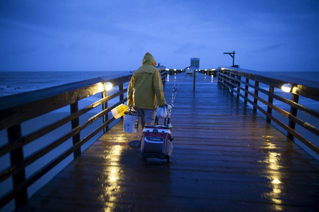 Fisherman Dominick Manfredini prepares to fish at daybreak at the pier at Myrtle Beach State Park as heavy rain falls in Myrtle Beach, South Carolina, October 2, 2015. Rapidly changing weather con ...